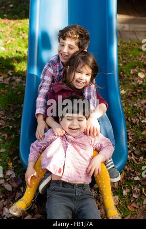 Siblings in a row between each others legs on playground slide smiling - Stock Photo