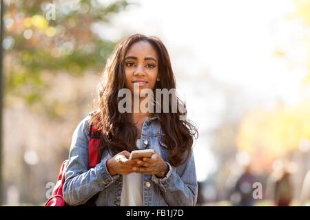 Young woman with long brown hair wearing denim jacket  holding smartphone looking away smiling