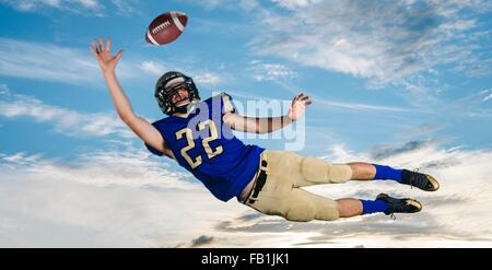 Male teenage American football player reaching to catch ball mid air against blue sky - Stock Photo