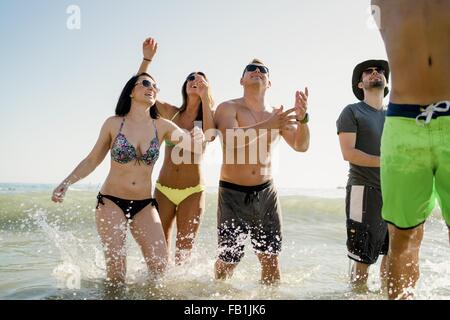 Five adult friends playing American football in sea at Newport Beach, California, USA - Stock Photo