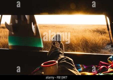 Male surfer with feet up in back of jeep at sunset, San Luis Obispo, California, USA - Stock Photo