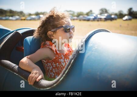 Girl sitting in barrel cart, wearing sunglasses looking away - Stock Photo