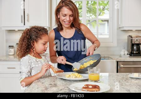 Mother at kitchen counter serving daughter scrambled eggs from frying pan - Stock Photo