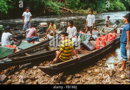 River boat drivers who take tourists into the Taman Negara national park in Malaysia sit on their boats on the shore - Stock Photo
