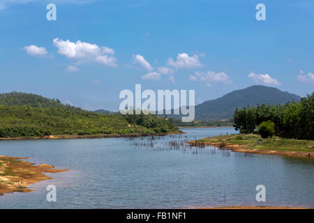 Remote lake in the Malaysian Peninsula. S shaped lake surrounded by jungle slopes. Sand and mud banks line the waters - Stock Photo