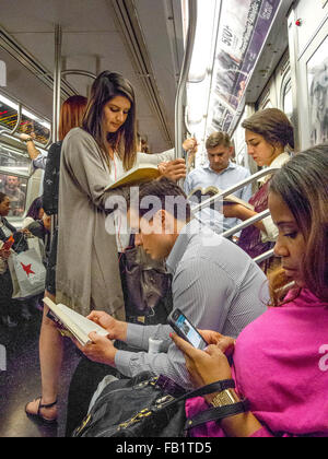 New York City subway passengers read books as they travel while a woman in the foreground reads from a cell phone. - Stock Photo