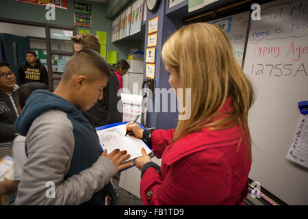 A San Clemente, CA, middle school teacher signs a male teenage student's attendance sheet. - Stock Photo