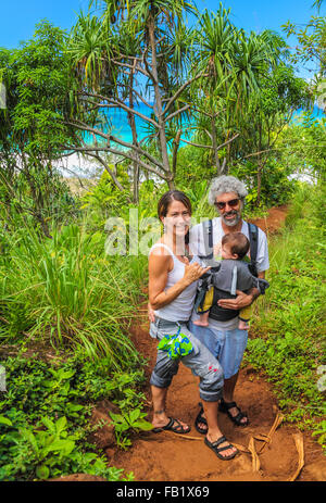 Couple with baby on the Kalalau Trail, with Hanakapiai Beach in background - Stock Photo