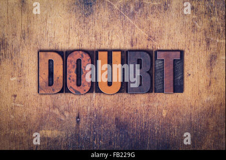 The word 'Doubt' written in dirty vintage letterpress type on a aged wooden background. - Stock Photo