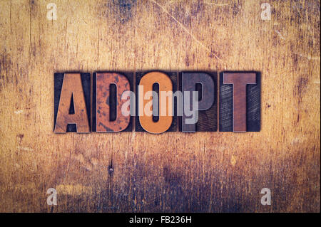 The word 'Adopt' written in dirty vintage letterpress type on a aged wooden background. - Stock Photo
