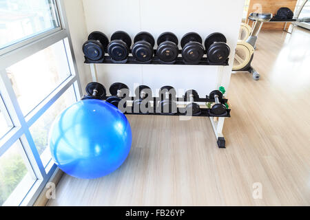 Focus down on dumbbells on shelves and big blue aerobic ball in gym with floor space - Stock Photo