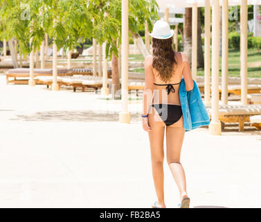 Slim woman in black bikini walking at the poolside along sun loungers. Summer resort background - Stock Photo