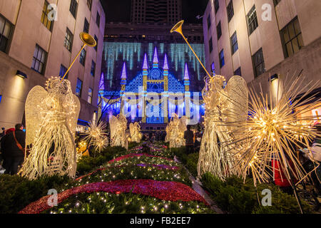 Christmas Angels at Rockefeller Center Channel Gardens with Saks department store's Christmas light show behind, - Stock Photo
