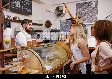 Shot of a young women friends placing an order in a coffee shop. Waiter taking coffee order from two young female - Stock Photo