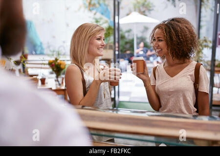Indoor shot of two young female friends having a cup of coffee at cafe. Women at restaurant drinking hot coffee - Stock Photo