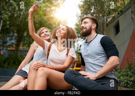 Three young friends taking a selfie with cellphone. Multiracial group of young people having fun together while sitting outdoors