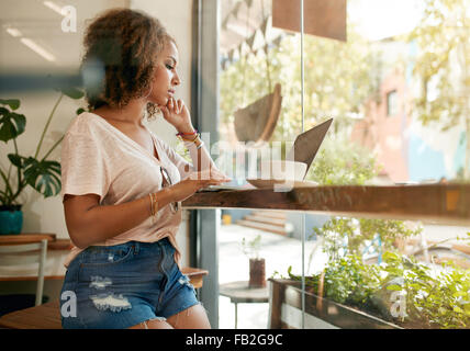 Shot of a young woman using her laptop in a coffee shop. African female sitting in cafe surfing internet on her laptop.