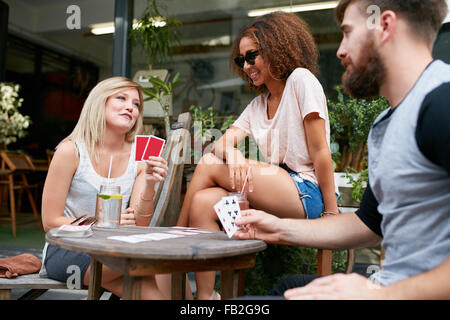 Young people playing cards at sidewalk cafe. Three friends playing poker at outdoor coffee shop. Stock Photo