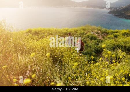 Couple hiking towards the coastline, walking on pathway through grassland, on a summer day. - Stock Photo
