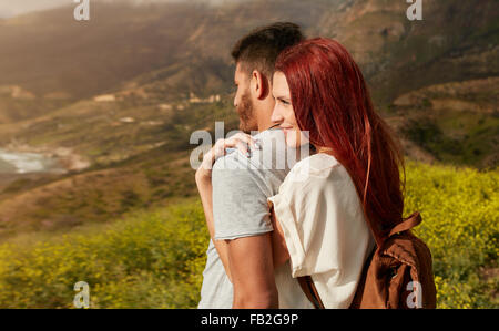 Romantic young couple enjoying the sights while hiking through the mountain. Young woman embracing his boyfriend - Stock Photo