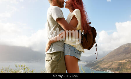 Cropped shot of young man and woman standing close to each other face to face. Romantic couple embracing outdoors. - Stock Photo
