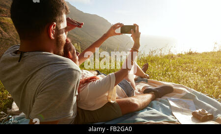 Rear view of young couple on picnic taking a self portrait with their smart phone. - Stock Photo