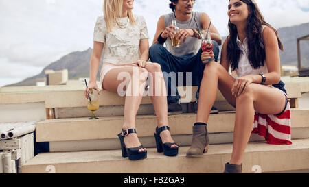 Cropped shot of young friends sitting on steps and having cocktails during a party. Young people having a rooftop - Stock Photo