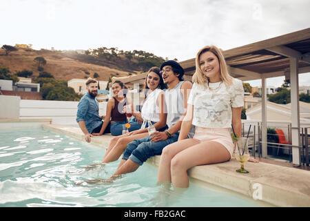 Smiling young woman looking at camera with her friends sitting on the edge of swimming pool. Young people enjoying - Stock Photo