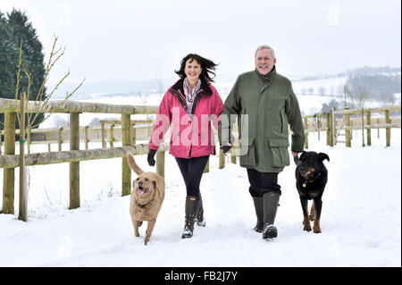 Middle aged couple walking their dog in a winter countryside - Stock Photo