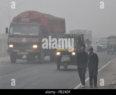 New Delhi. 8th Jan, 2016. Photo taken on Jan. 8, 2016 shows vehicles and pedestrians in dense fog in Faridabad, - Stock Photo