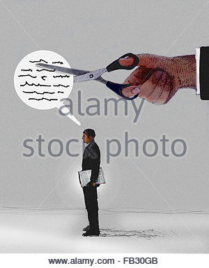 Large hand with scissors cutting words in speech bubble of businessman - Stock Photo