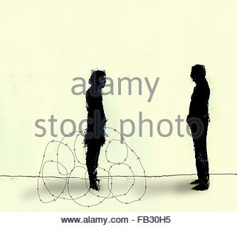 Man facing woman surrounded by barbed wire - Stock Photo