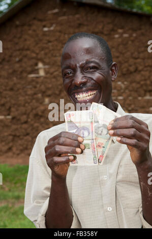 Happy Kenyan farmer holding banknotes earned by selling milk from his cow. Kenya. - Stock Photo