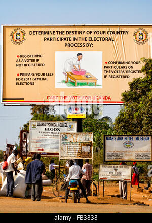 Mbale, Uganda - Villagers passing by a Ugandan outdoor poster issued bz the Election Commission calling to participation - Stock Photo