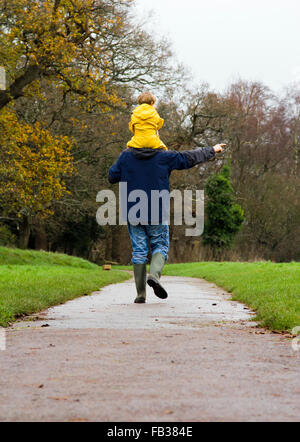 Father and son taking a winter walk in a park in Bristol, UK - Stock Photo