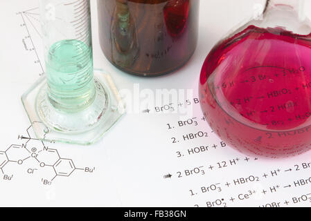 Laboratory glassware with reagents on a paper with chemical formulas - Stock Photo