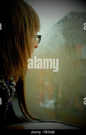 Young woman wearing glasses looking thoughtfully out through a misted up and rain covered train window whilst at - Stock Photo