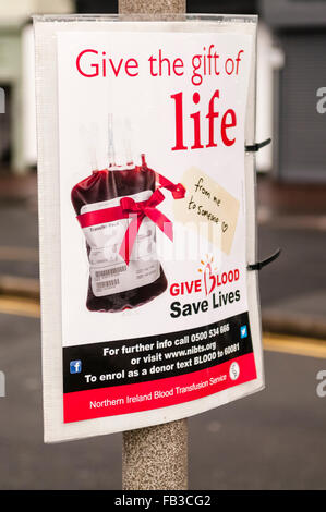 Sign on a lamppost advising the public that blood donation sessions will be taking place. - Stock Photo