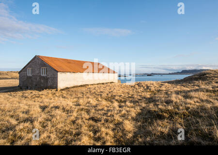 Old Icelandic shelter on a farm near a fjord - Stock Photo