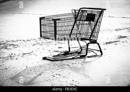 High contrast black and white image of shopping cart abandoned in snow by the shopper. - Stock Photo