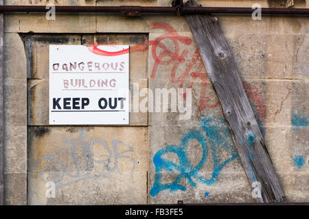 Dangerous Building Keep Out sign. A peeling warning sign on abandoned houses, offering a warning to people - Stock Photo