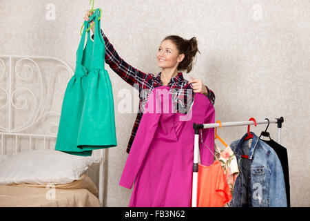 Smiling girl holds two dresses while choosing closes - Stock Photo