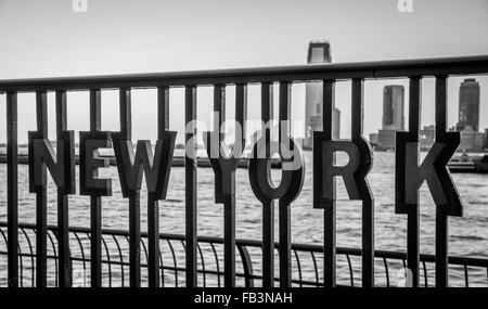 Close up 'New York' inset into metal railings at the World Financial Center Plaza with the Hudson river and Jersey - Stock Photo