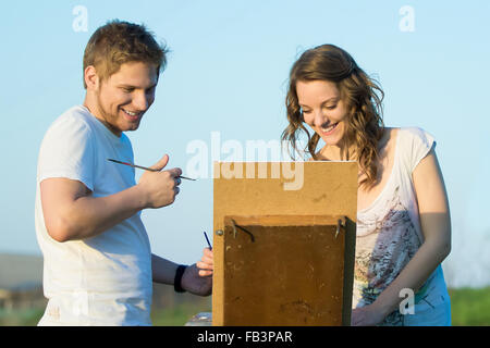 Couple on the date outdoors has fun drawing - Stock Photo
