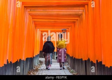 Women in traditional kimono walking along the Senbon Torii (thousands of Torii gates) in Fushimi Inari Shrine, Kyoto, - Stock Photo