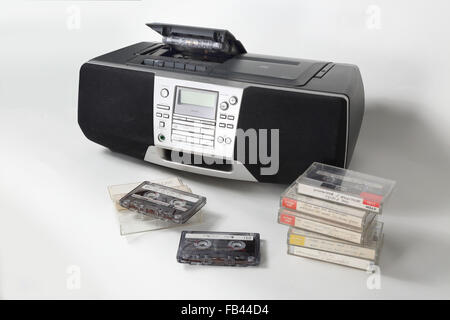 Home recorded cassette tapes stacked up in front of a 1990s style cassette, radio and and CD player - Stock Photo