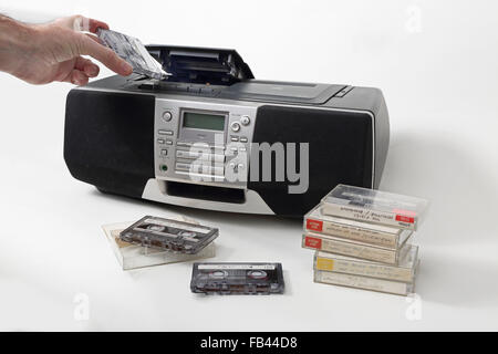 A home-recorded cassette tape is loaded into a1990s style cassette, radio and and CD player. Tapes stacked in the - Stock Photo