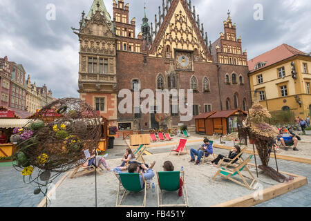 Tourists sitting outside East side of Wroclaw Gothic Town Hall, Market Square, Old Town, Wroclaw, Poland - Stock Photo