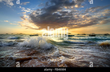 Fishing boats in the ocean at sunset - Stock Photo