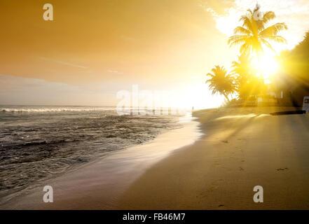 Orange sky over ocean and sandy beach - Stock Photo